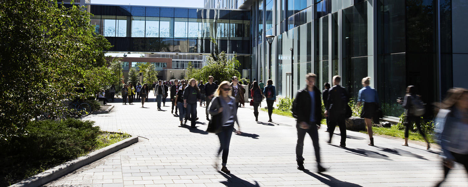 Students walking through UCalgary Quad by the Taylor Family Digital Library