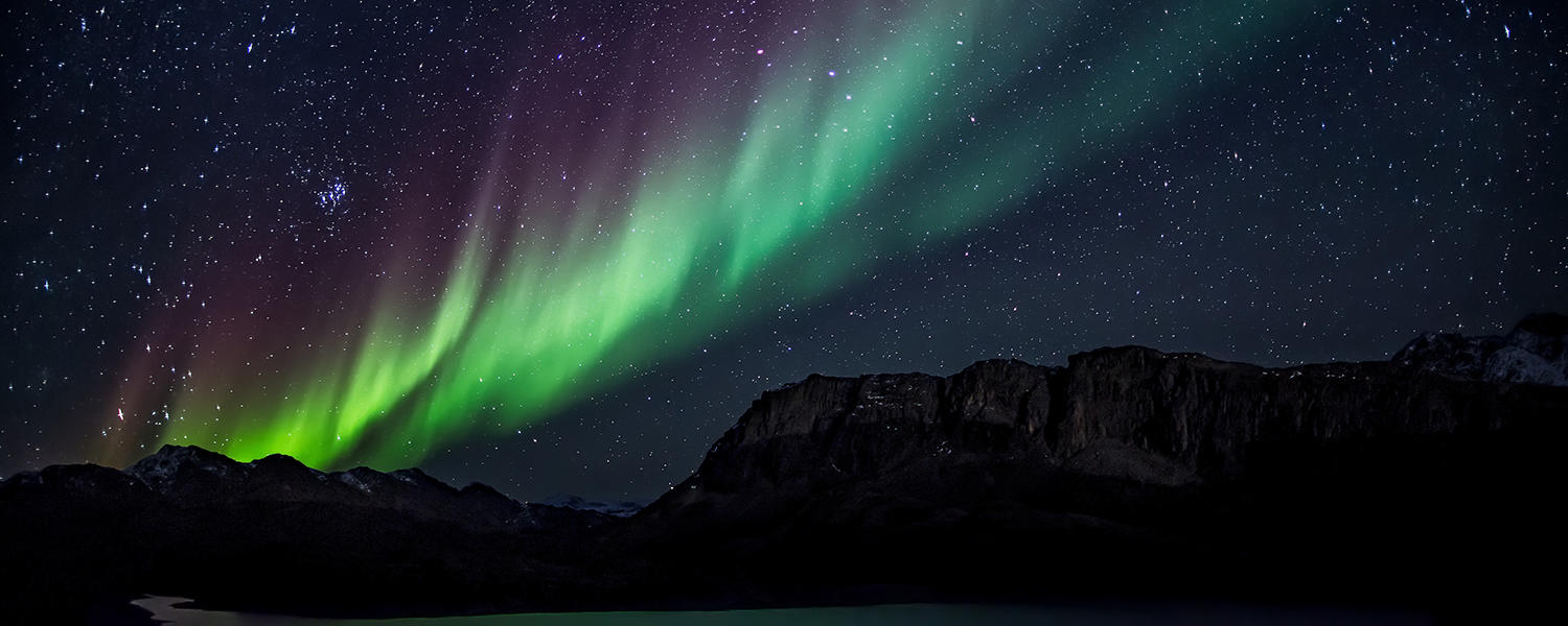 Mountain range under northern lights.
