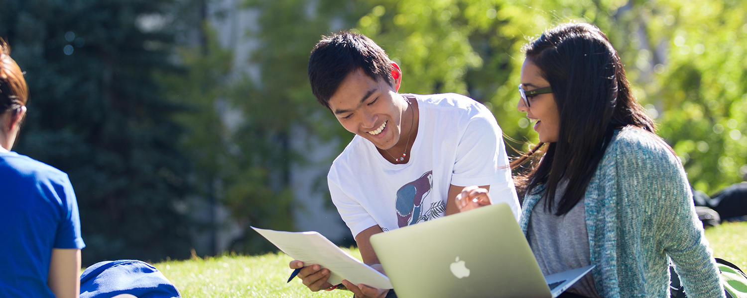 Two students study together outdoors.