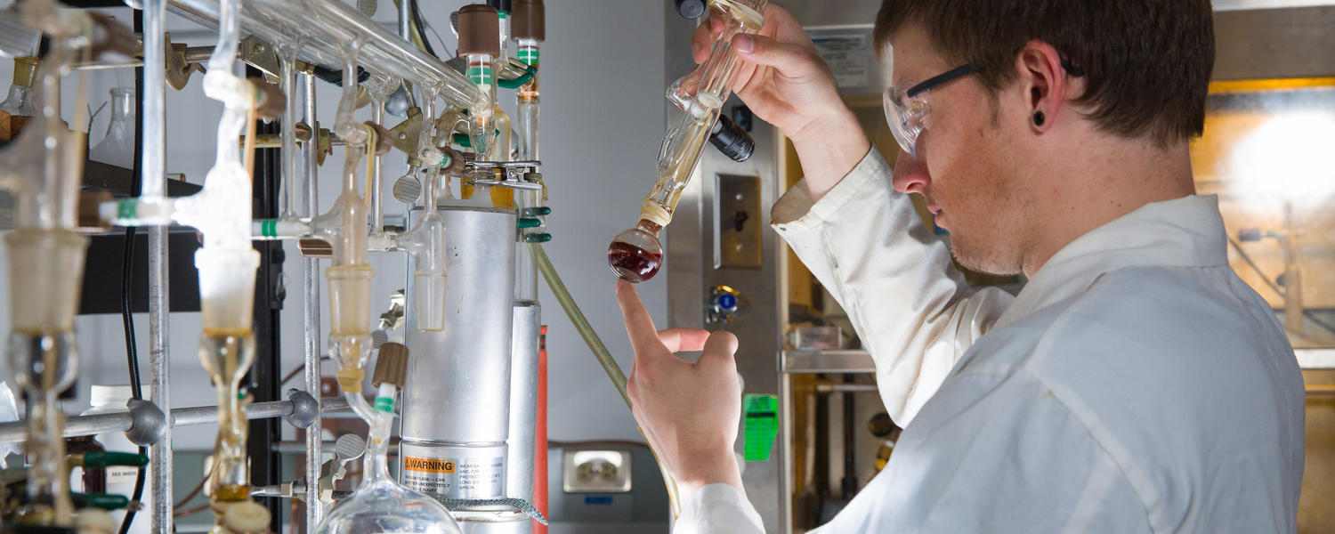 A male student wearing a white lab coat examines a beaker
