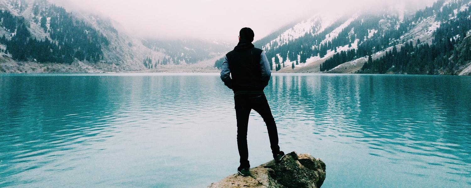 A person stands on a rock beside a mountain lake.