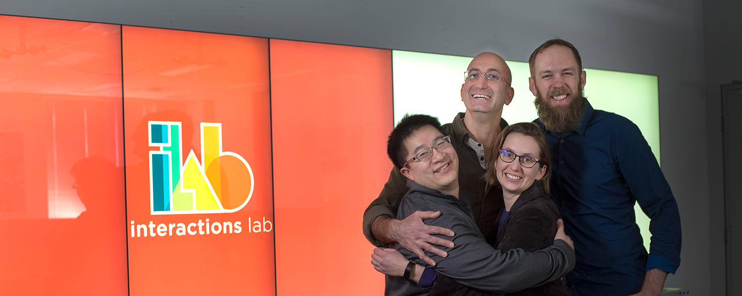 Four professors stand together in the iLab.