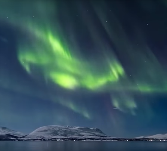 The northern lights appear in a dark sky over snow-covered hills