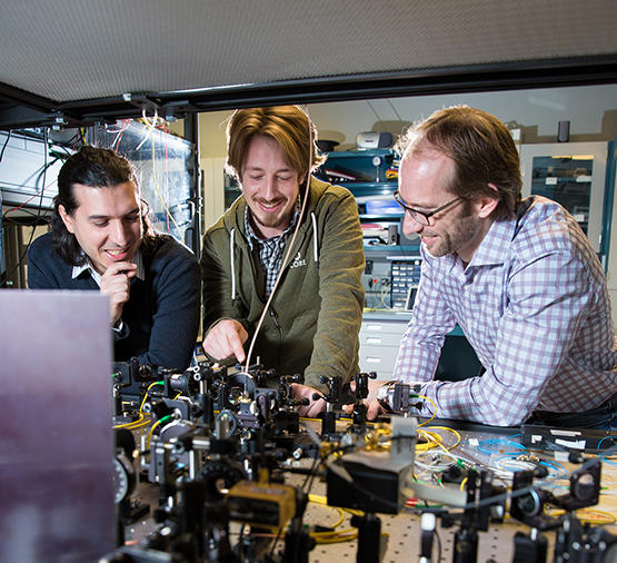 Three male researchers stand in front of a quantum computer