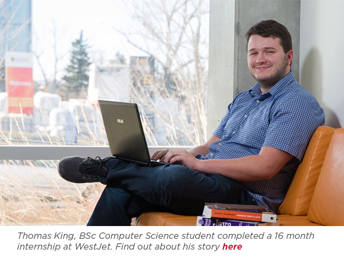 Student Thomas King sitting on couch with computer