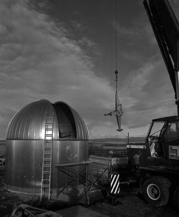 Image of a crane lowering a piece of a telescope frame into the open door of a telescope dome at the Rothney Astrophysical Observatory at Priddis in 1971.