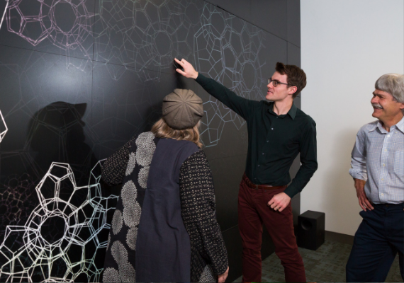 A group of people interact with a digital display.
