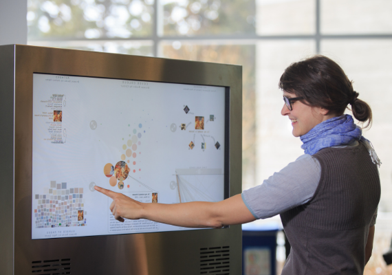 A female grad student touches the Bohemian Bookshelf touchscreen in the TFDL