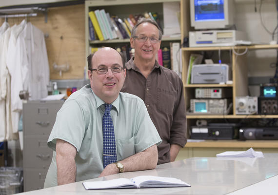 Two faculty members smile for the camera.