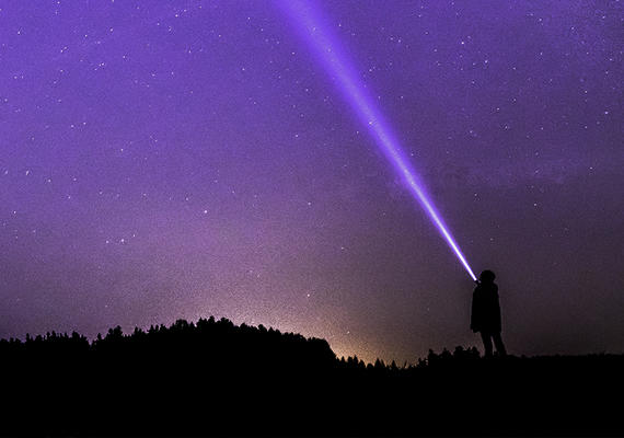 A person shines a flashlight at the sky.