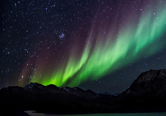 Northern lights over mountain range.