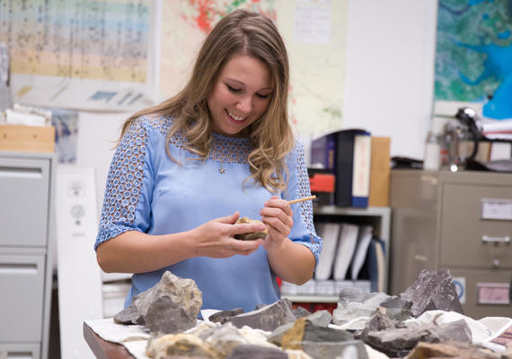 A smiling student holds a fossil in a paleontology lab