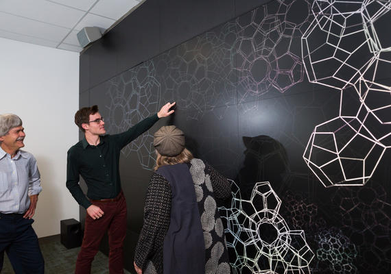 A graduate student points to molecule structure in the TFDL visualization studio