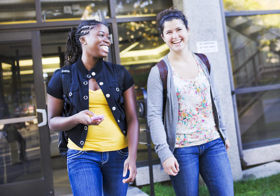 Two female students walk outdoors together.