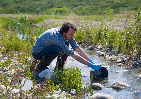 Male grad student takes a stream sample at the ACWA facility.