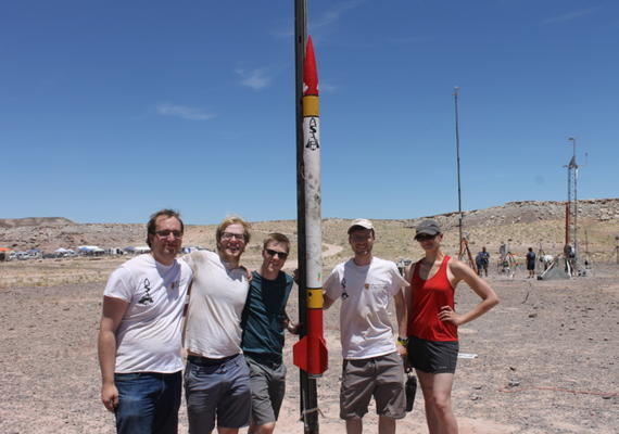 Students pose with a rocket at a test launch in Utah