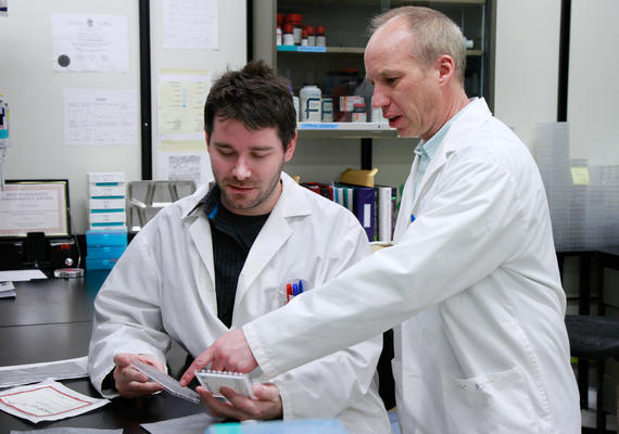 Two male scientists work together.