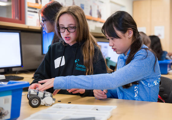 Two grade school students build a robot.
