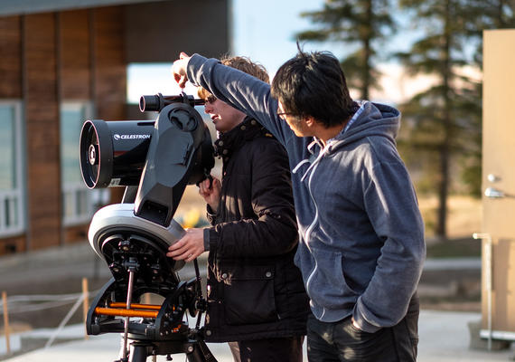Two students using a telescope.