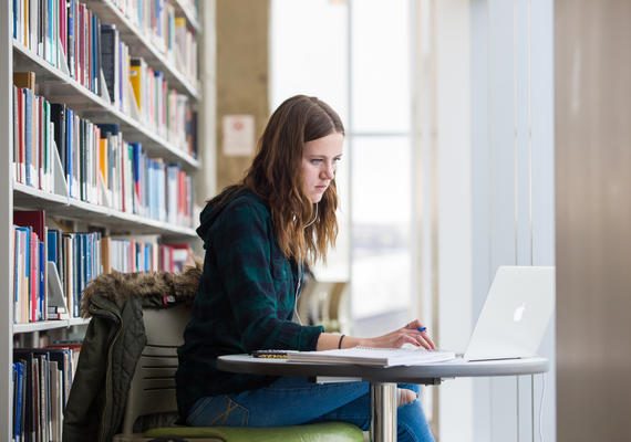 Femail student sitting at desk in library