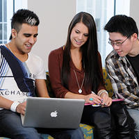 Three students looking at computer