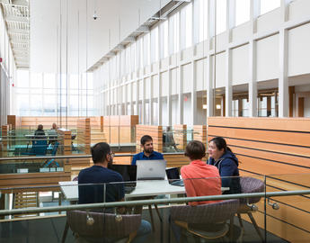 A group of instructors sit in a learning pod inside the Taylor Institute for Teaching and Learning