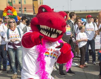 University of Calgary mascot Rex, a red tyrannosaurus, wears UCalgary pride regalia at the Calgary Pride Parade. He is pointing at the camera.