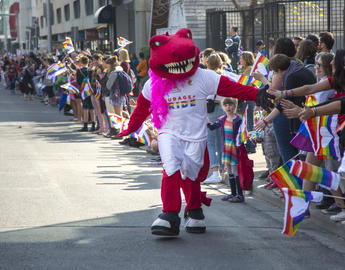 "UCalgary mascot Rex ""high-fives"" the crowd at the 2018 Calgary Pride parade"