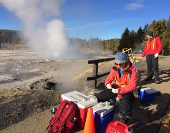A female geoscience researcher takes samples at a geyser in Yellowstone Park