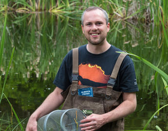 A male grad student in waders stands in a stream.