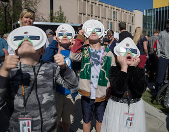 Children wearing homemade viewing glasses watch the solar eclipse at the Rothney Astrophysical Observatory's pop-up observatory on the University of Calgary campus in 2017