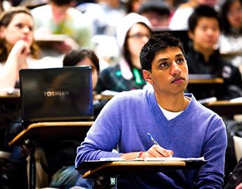A male student takes notes during a lecture.