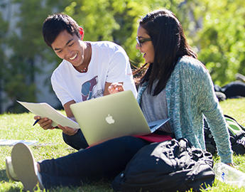 Two students study outdoors together.