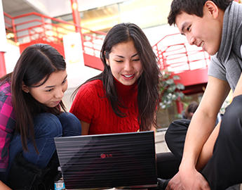 A trio of students sit together around a laptop.