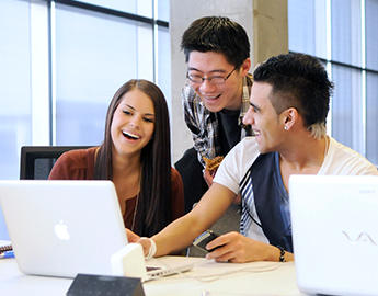 Three students gather around a laptop.