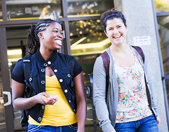 Two female students walk outdoors on campus.