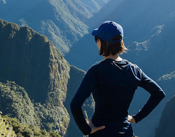 A young woman overlooks Machu Picchu.