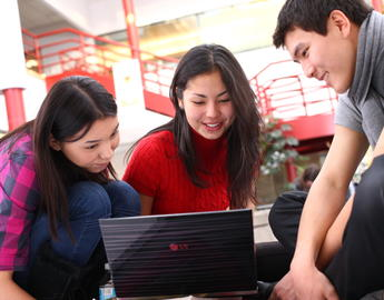 Two female students and a male student look at a laptop screen together