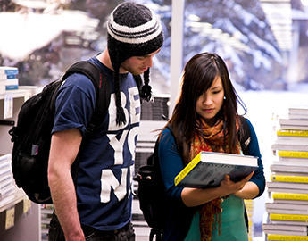 Two students look at textbooks.