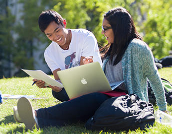 Two students study outdoors.