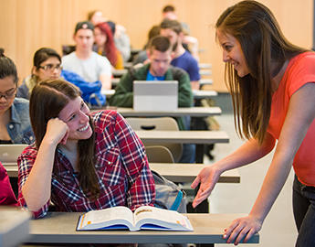 Two female students smile while studying together.