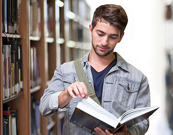 A young man holding an open book in a library