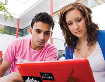 A young man and a young woman look at a laptop