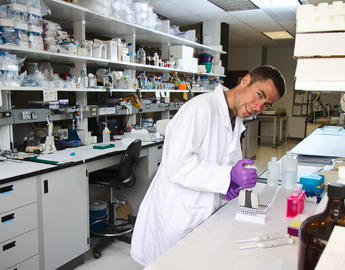A male scientist leans over his work.