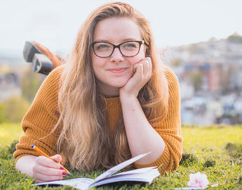 A girl studies outside on the grass.