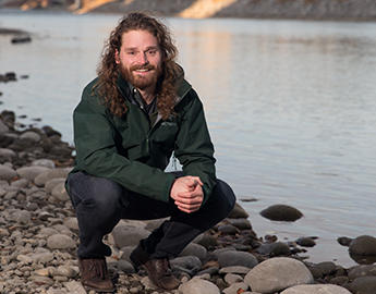 A male graqduate student crouches beside the shore.