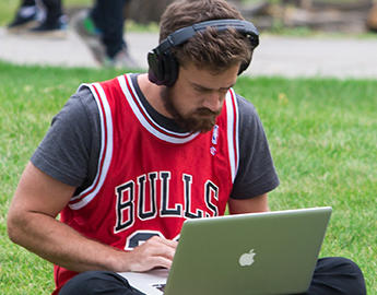 A male student uses a laptop outdoors.