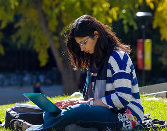 A female student studies outdoors.